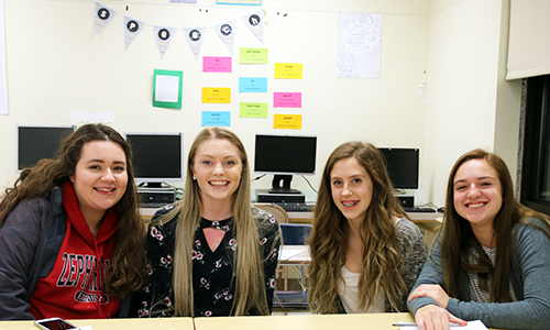Four student girls smiling sitting in front of computers.